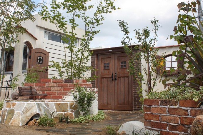 カンナと白の板塀とレンガの花壇と園路。