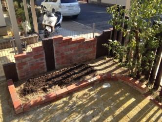 レンガとコンクリート製枕木で花壇を新設。隣地への水はねを防ぎます。
